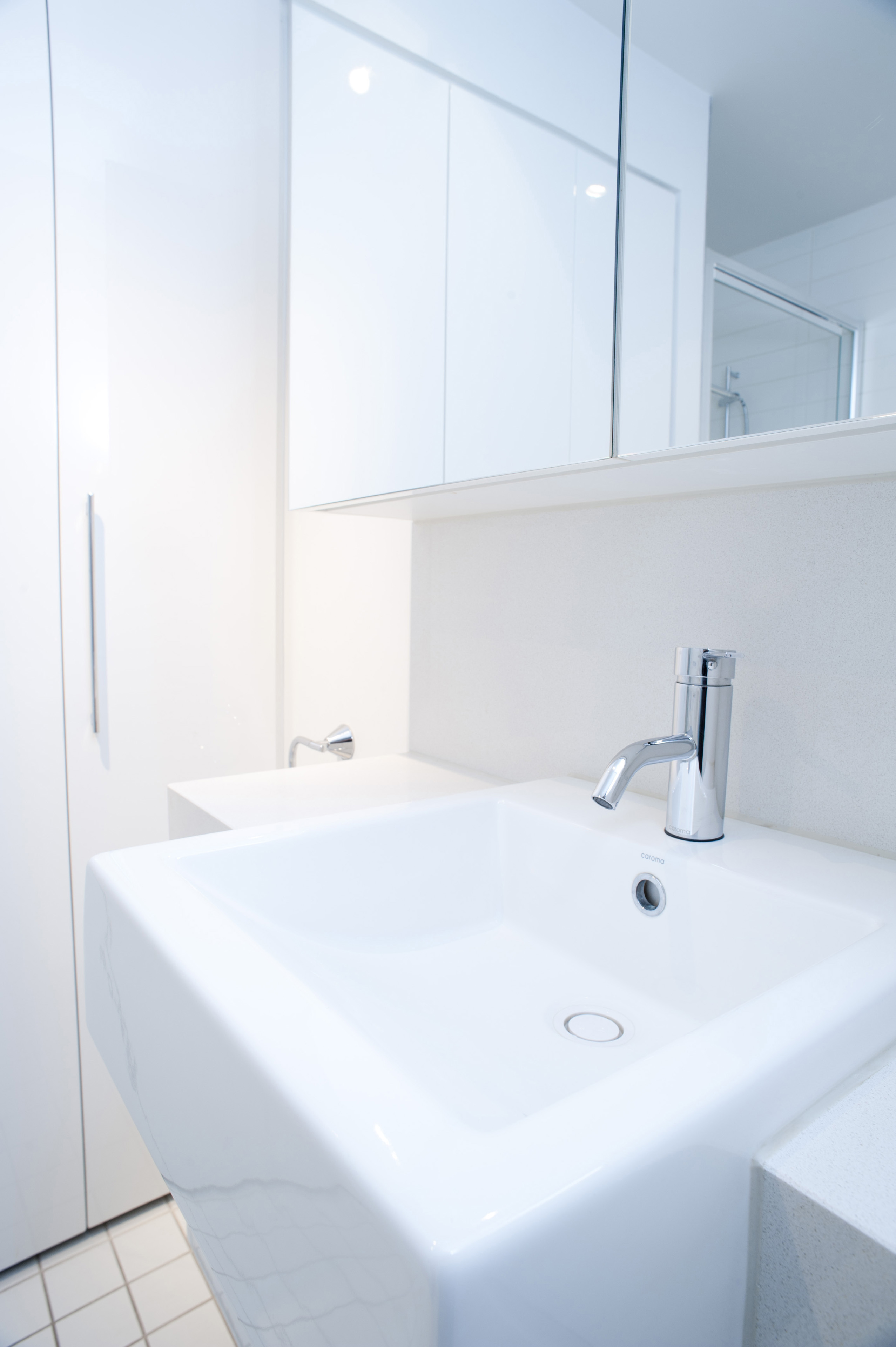 Close up interior view of a plain white handbasin and metal faucet in a white monochrome bathroom